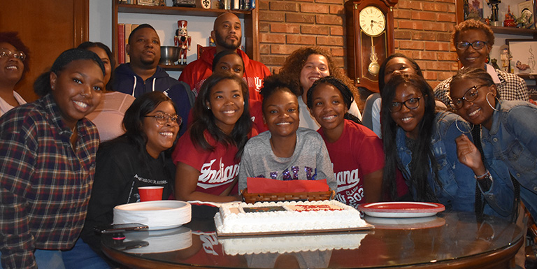 A big group of students smiling behind a cake.