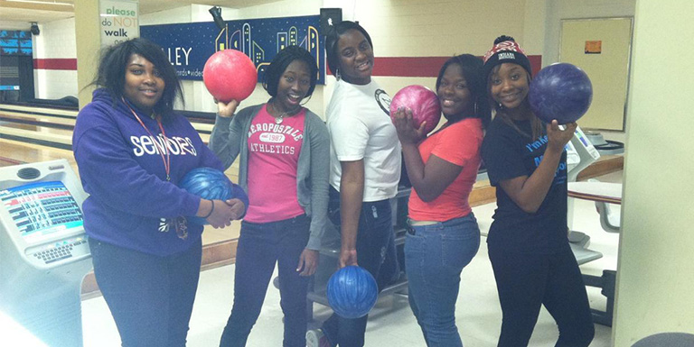 Five students in a bowling alley posing with their bowling balls.