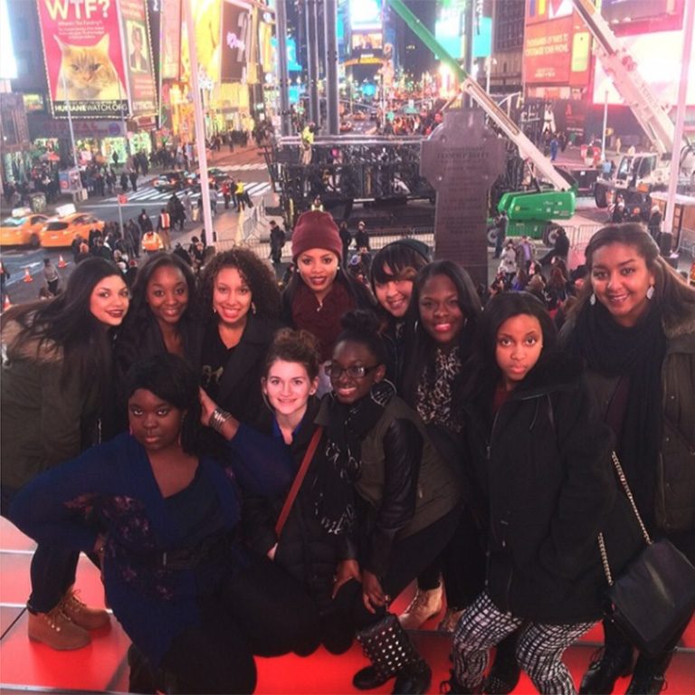 A large group of students posing for the camera in Time Square.